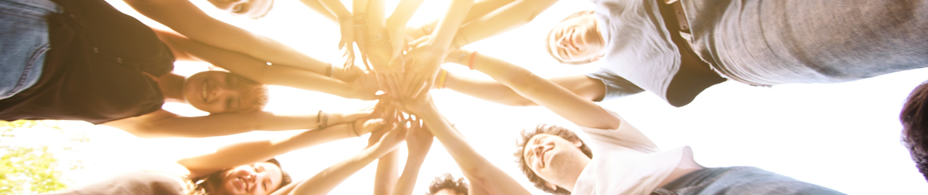 Group of people standing in a circle with their hands intertwined